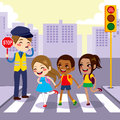 School children pedestrian crossing three cute little students street walking through with help from male cop holding Stock Photo