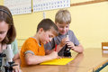 School children in a yellow classroom during a lesson in biology they are working with microscope for scientific methods Royalty Free Stock Photography