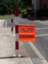School crossing bright orange children flag displayed on red and white striped post Stock Photography