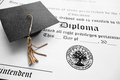 School diploma and mini graduation cap Royalty Free Stock Photo