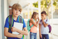 School friends bullying a sad boy in corridor Royalty Free Stock Photo