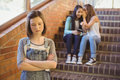 School friends bullying a sad girl in school corridor Royalty Free Stock Photo