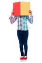 School girl hiding her face behind a notebook shy little with Stock Image
