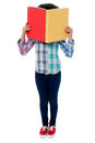 School girl hiding her face with a book shy behind colored notebook Royalty Free Stock Images