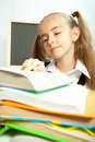 School girl making homework behind stack of books. Royalty Free Stock Photo
