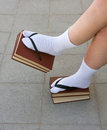 School girl teenager with books as flip flops Stock Photos