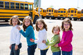 School girls friends in a row walking from school bus sisters yellow lot Royalty Free Stock Photo