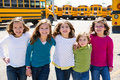 School girls friends in a row walking from school bus sisters yellow lot Royalty Free Stock Images
