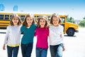 School girls friends in a row walking from school bus sisters yellow lot Royalty Free Stock Photography