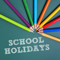 School holidays coloured pencils of different colors and text writtten in a green chalkboard Royalty Free Stock Image