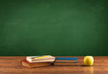 School items on desk with empty chalkboard Royalty Free Stock Photo