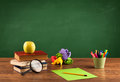 School items on desk with empty chalkboard Royalty Free Stock Photo