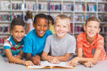 School kids reading book together in library Royalty Free Stock Photo