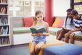 School kids sitting on sofa and reading book in library Royalty Free Stock Photo