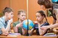 School kids studying a globe together with teacher Royalty Free Stock Photography