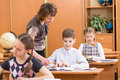 School kids and teacher at lesson work controlling learning process Royalty Free Stock Photos