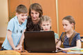 School kids and teacher using laptop at lesson schoolchildren Stock Image