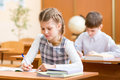 School kids writing to copybook at lesson schoolchildren Royalty Free Stock Image