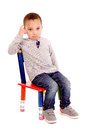 School little boy sitting in chair isolated in white Stock Image
