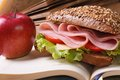 School lunch: a ham sandwich and an apple on open notebook Royalty Free Stock Photo