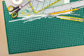 School and office supplies on green cutting mat board background Royalty Free Stock Photo