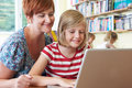 School Pupil With Teacher Using Laptop Computer In Classroom Royalty Free Stock Photo