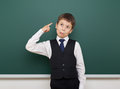 School student boy posing at the clean blackboard, grimacing and emotions, dressed in a black suit, education concept, studio phot Royalty Free Stock Photo