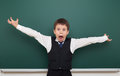 School student boy posing at the clean blackboard and open arms, grimacing and emotions, dressed in a black suit, education concep Royalty Free Stock Photo
