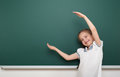 School student girl open arms at the clean blackboard, grimacing and emotions, dressed in a black suit, education concept, studio Royalty Free Stock Photo