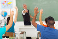 School students classroom group of with hands up in during a lesson Stock Photo