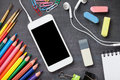 School supplies and smartphone on blackboard background Royalty Free Stock Photo
