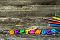 School supplies on wooden background colorful pencils with the word september Stock Photo