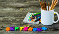 School supplies on wooden background a mug of crayons and notepad word september with the Royalty Free Stock Photos