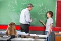 Schoolboy asking question to teacher while solving side view of little mathematics on board in classroom Stock Images