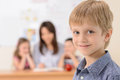 Schoolboy cheerful smiling at camera while teacher with pupils sitting on the background Royalty Free Stock Images