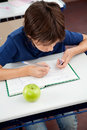Schoolboy copying from cheat sheet during high angle view of at desk examination Stock Images