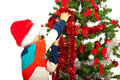 Schoolboy decorate christmas tree and wearing colorful clothes and santa hat Stock Photography