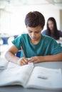 Schoolboy doing homework in classroom Royalty Free Stock Photo