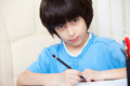 Schoolboy doing homework with pen Royalty Free Stock Photo
