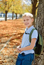Schoolboy in fall with backpack after school park near the tree Royalty Free Stock Photography