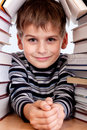 Schoolboy and a heap of books on white background Royalty Free Stock Photography