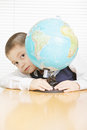 Schoolboy hiding behind globe Stock Images