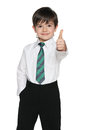 Schoolboy holds his thumb up a on the white background Royalty Free Stock Photography