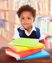 Schoolboy in library portrait of little african sitting and reading different colourful books doing homework back to school Stock Photos