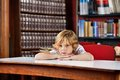 Schoolboy looking away while leaning on table bored little in library Stock Images