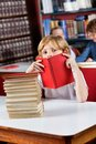 Schoolboy peeking through book in library portrait of cute little while sitting with stack of books at table Stock Photo