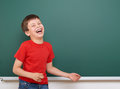 Schoolboy play and laugh near a blackboard, empty space, education concept Royalty Free Stock Photo
