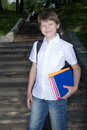 Schoolboy portrait the in white shirt with books and writing books in hands Stock Image