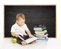 Schoolboy reading book near blackboard kindergarten school boy little child on black board background elementary education concept Royalty Free Stock Images