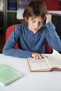 Schoolboy reading book at table little in library Stock Photography